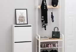 Biały wieszak do przedpokoju z półkami na buty i ławką.